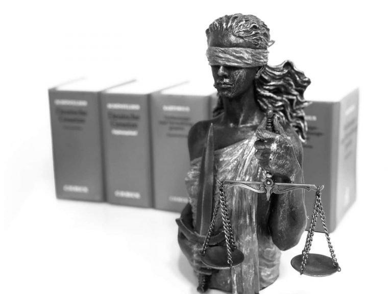 Justizia mit Büchern im Hintergrund